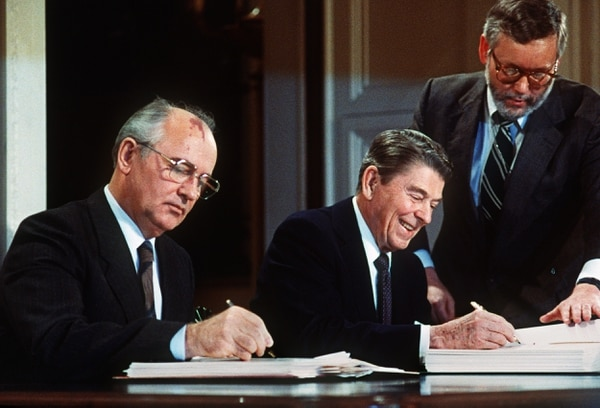 Soviet leader Mikhail Gorbachev, left, and U.S. President Ronald Reagan sign on Dec. 8, 1987, a treaty eliminating U.S. and Soviet intermediate-range and shorter-range nuclear missiles. (AFP via Getty Images)