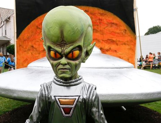 A figure representing a green alien is positioned in front of the permanent flying saucer replica in Mars, Pa., in June 2015. (Keith Srakocic/AP)