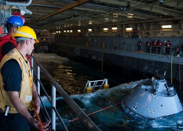 Seaman Marc Castillejo handles a line from NASA's Orion test article aboard the Anchorage. (MC2 Carrel Regis/Navy)