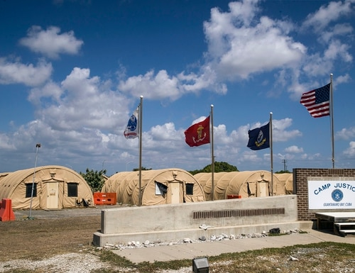 In this April 18, 2019, file photo, in this photo reviewed by U.S. military officials, flags fly in front of the tents of Camp Justice in Guantanamo Bay Naval Base, Cuba. (Alex Brandon/AP)