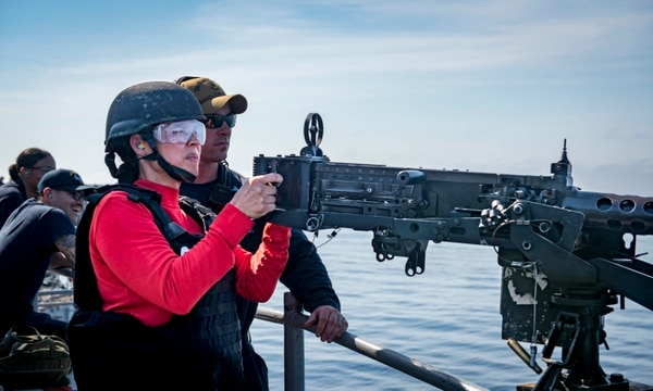 Lt. Cmdr. Karen Sankes-Ritland aims at a target with a .50-caliber machine gun during a live-fire exercise on board the aircraft carrier George H.W. Bush on June 10. (Mass Communication Specialist 3rd Class Joe Boggio/Navy)
