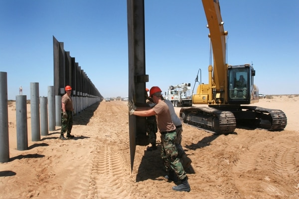 Airmen with the 177th Civil Engineer Squadron guide a 1,400 pound panel into place along the United States-Mexico border, Aug. 22, 2007, in support of Operation Jump Start. (Air National Guard)