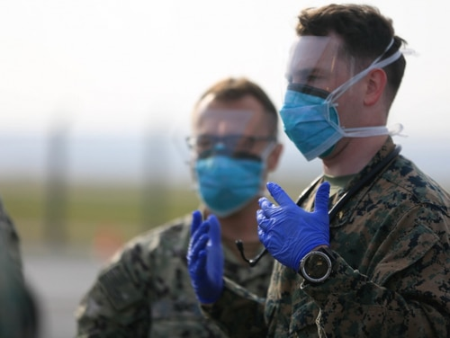 Medical personnel direct U.S. Marines with 1st Battalion, 25th Marine Regiment as they arrive at Kadena Air Base, Okinawa, Japan, on Feb. 28, 2020. Upon their return from the Republic of Korea, the Marines were screened in accordance with U.S. Centers for Disease Control and Japanese government guidelines. III MEF is taking its responsibilities to protect our Marines, Sailors, families, and local communities safe by actively working to prevent the further spread of COVID-19. (U.S. Marine Corps photo by Cpl Josue Marquez)