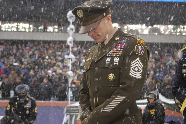 Sergeant Major of the Army Dan Dailey bows in prayer prior to kickoff at the Army-Navy game at Lincoln Financial Field in Philadelphia on Dec. 9, 2017. SMA Dailey wore the Army's proposed 'Pink and Green' daily service uniform, modeled after the Army's standard World War II-era dress uniform. (Ronald Lee/Army)