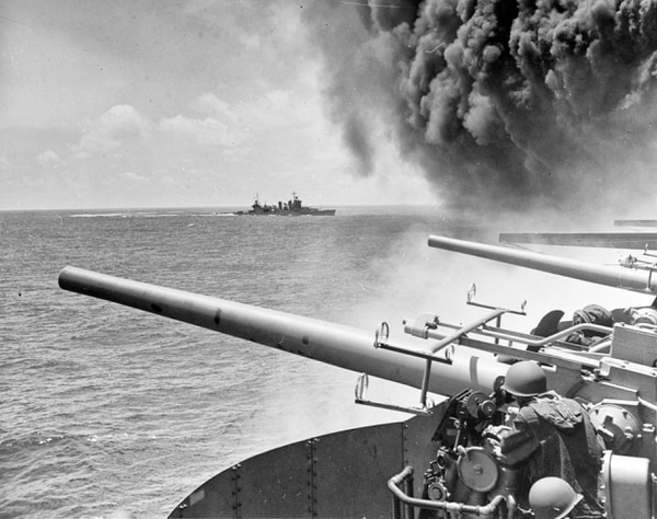On June 4, 1942, the the heavy cruiser Astoria steams by their aircraft carrier Yorktown, shortly after the carrier had been hit by three Japanese bombs in the battle of Midway. (William G. Roy/Navy via AP)