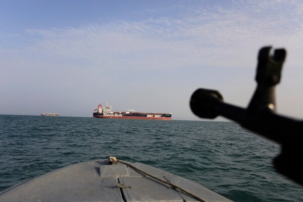 In this July 21, 2019 photo, a speedboat of Iran's Revolutionary Guard trains a weapon toward the British-flagged oil tanker Stena Impero, which was seized in the Strait of Hormuz on Friday by the Guard, in the Iranian port of Bandar Abbas. (Morteza Akhoondi/Tasnim News Agency via AP)