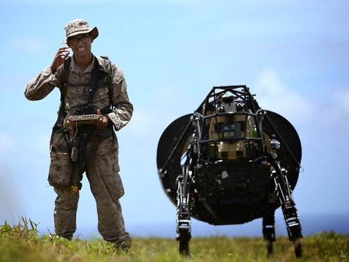 A Marine leads the Legged Squad Support System through a grassy area at Kahuku Training Area. Futuristic measures to combat enemies are explored in a sci-fi writing program implemented by the Marines (Cpl. Matthew Callahan/Marine Corps).