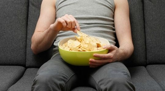 A man on a couch eating potato chips (Getty Images)