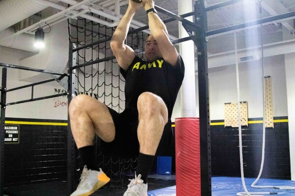 Spc. Juan Gonzalez performs a leg tuck. (Staff Sgt. James Avery/Army)