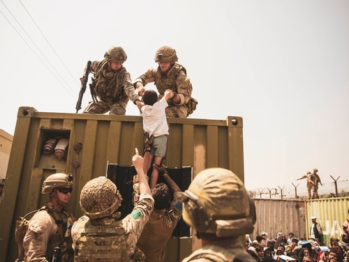 UK coalition forces, Turkish coalition forces and U.S. Marines assist a child during an evacuation at Hamid Karzai International Airport, Kabul, Afghanistan, Aug. 20. (Staff Sgt. Victor Mancilla/Marine Corps)