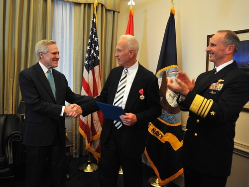 141216-N-ZI511-951 WASHINGTON (Dec. 16, 2014) Secretary of the Navy (SECNAV) Ray Mabus and Chief of Naval Operations (CNO) Adm. Jonathan Greenert present the Legion of Merit posthumously to Lt. Cmdr. Herbert Claudius for his actions on July 30, 1942. His son Herbert Gordon Claudius Jr., center, at a ceremony at the Pentagon, accepted the award. The actions of Lt. Cmdr. Claudius as commanding officer of PC-566 resulted in the sinking of enemy submarine U-166. (U.S. Navy photo by Chief Mass Communication Specialist Julianne F. Metzger/Released)