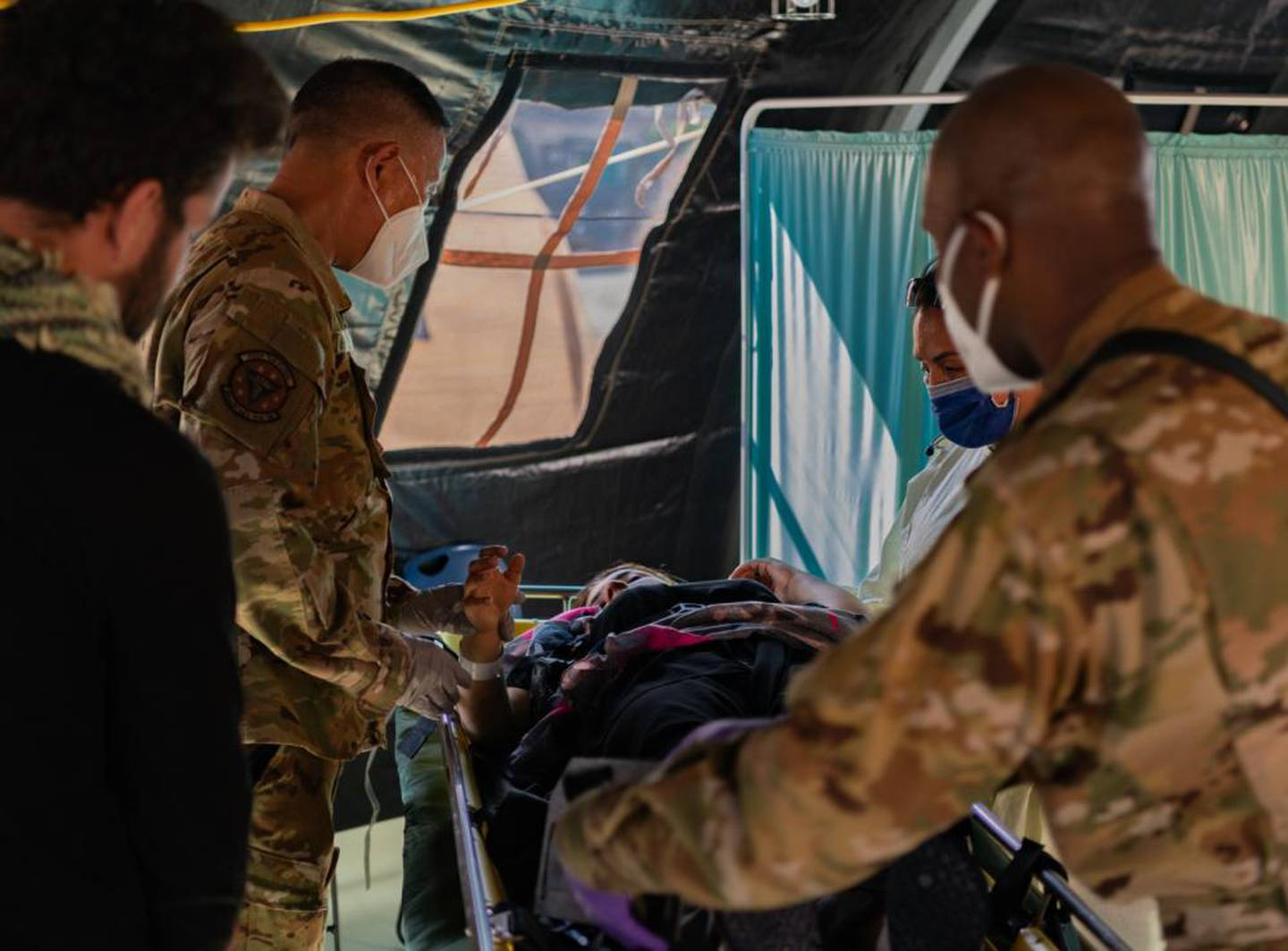 Airmen assigned to the 86th Medical Group provide post-labor care to an Afghan mother who gave birth aboard a U.S. Air Force C-17 Globemaster III, call sign Reach 828, with the aid of U.S. Army Captain Erin Brymer, Landstuhl Regional Medical Center registered nurse, upon landing at Ramstein Air Base, Germany, Aug. 21. During an evacuation flight from an Intermediate Staging Base in the Middle East, the mother went into labor and began experiencing complications due to low blood pressure. The aircraft commander made the decision to descend in altitude to increase air pressure in the aircraft, which helped stabilize and save the mother's life. Upon landing, Capt. Brymer and 86th Airlift Wing medics came aboard and delivered the child in the cargo bay of the aircraft. The baby girl and mother were transported to a nearby medical facility and are in good condition. (Airman Edgar Grimaldo/Air Force)