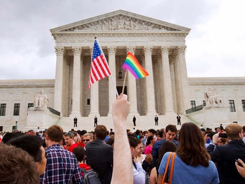 In this June 26, 2015, file photo, a man holds a U.S. and a rainbow flag outside the Supreme Court in Washington after the court legalized gay marriage nationwide. (Jacquelyn Martin/AP)