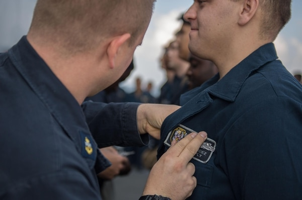 Sailors receive their Enlisted Surface Warfare Specialist pin on board the guided-missile cruiser Mobile Bay in the Arabian Sea on Dec. 16. (Mass Communication Specialist 3rd Class Nick Bauer/Navy)