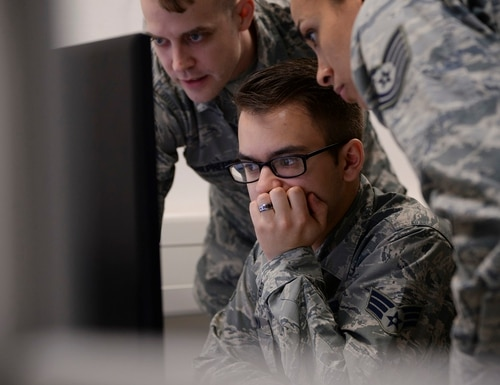 U.S. Airmen gather around a computer at the first U.S. Air Forces in Europe cyber-only exercise at the Warrior Preparation Center on Einsiedlerhof Air Station, Germany, May 10, 2018. The two-week long exercise, Tacet Venari, latin for silent hunt, pooled Airmen from four different units together forming mission defense teams, tasked with immobilizing adversaries through cyber defense. (U.S. Air Force photo by Airman 1st Class D. Blake Browning)