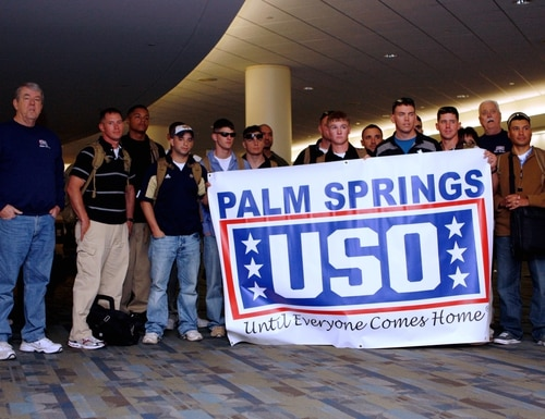 Service members pose for photos with the Palm Springs, Calif., United Service Organizations staff in 2010 at the Palm Springs International Airport. The USO airport center and others in the U.S. are being closed temporarily because of the coronavirus outbreak. (Lance Cpl. M.C. Nerl/Marine Corps)