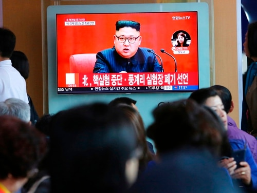 In this April 21, 2018, file photo, people watch a TV screen showing an image of North Korean leader Kim Jong Un during a news program at the Seoul Railway Station in Seoul, South Korea. The signs read: