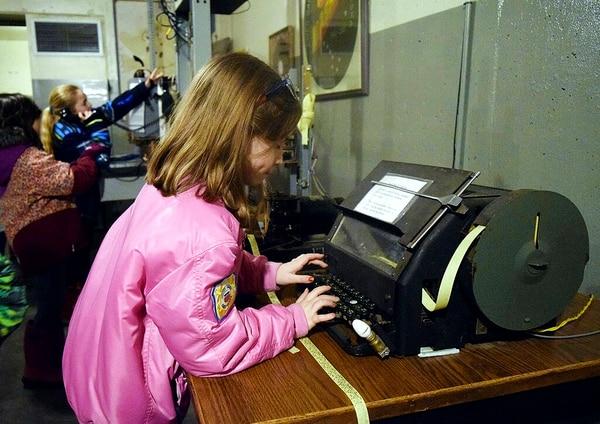 Peterson Elementary student Genevieve Garofalo tries out a WWII-era military typing device at the Kodiak Military History Museum at Fort Abercrombie State Historical Park in Kodiak, Alaska. (Jack Barnwell/Kodiak Daily Mirror via AP)
