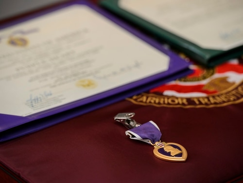 A purple heart lays on the table to be presented to Staff Sgt. Steve Tessitore during a Purple Heart Ceremony at the Center for the Intrepid, Brooke Army Medical Center, Dec. 19, 2014. Tessitore was shot in the neck while conducting a security patrol in Afghanistan, Nov. 14, 2014. (U.S. Air Force photo/Staff Sgt. Jonathan Snyder/Released)