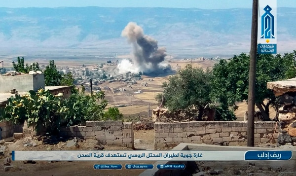 This photo released Tuesday, Sept 4, 2018 by the al-Qaida-affiliated Ibaa News Agency, shows smoke rising over buildings that were hit by airstrikes, in al-Sahan village, in the northern province of Idlib, Syria. Arabic reads,