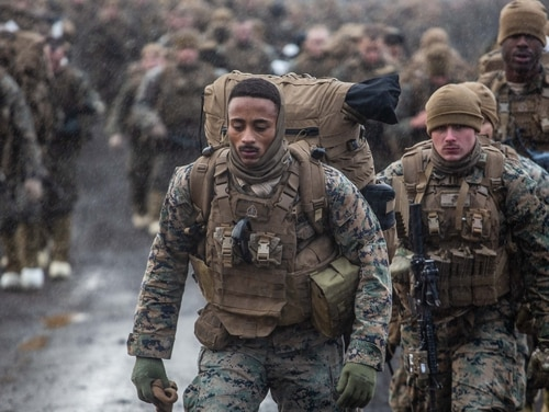 US Marines carry cold weather equipment as they begin to march across the Icelandic terrain. (Marine Corps)
