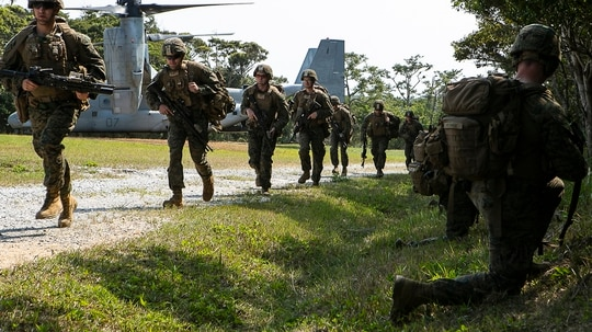 Marines with Charlie Company, Battalion Landing Team, 1st Battalion, 4th Marines, run toward security positions during a live-fire range as part of the 31st Marine Expeditionary Unit's simulated Expeditionary Advanced Base Operations, Camp Schwab, Okinawa, Japan, March 13, 2019. (Gunnery Sgt. T. T. Parish/Marine Corps)
