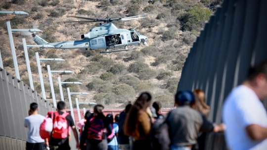 A Marine Corps helicopter flies past a pedestrian bridge after the closing of the United States-Mexico border was ordered on November 25, 2018 at the San Ysidro border crossing point south of San Diego, California. (Sandy Huffaker/AFP/Getty Images)