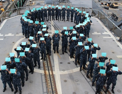 Sailors aboard the Ticonderoga-class guided-missile cruiser Chancellorsville gather on the flight deck to form a teal ribbon, in recognition of Sexual Assault Prevention (SAPR) Month. (Fire Controlman 2nd Class Monica Strickler/Navy)
