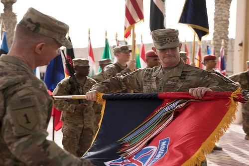 Maj. Gen. Walter Piatt, commander of the 10th Mountain Division from Fort Drum, New York, and Command Sgt. Maj. Samuel J. Roark uncase the division colors during the transfer of authority ceremony for Combined Forces Land Component Command-Operation Inherent Resolve in Baghdad, Iraq, March 19. (Staff Sgt. Michael Reinsch/Army)