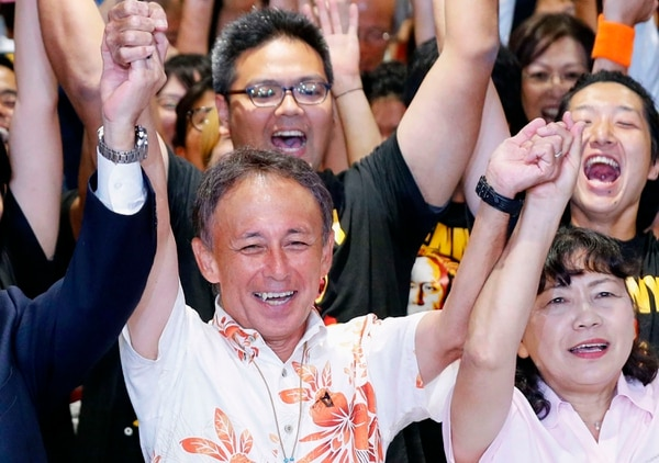 Japan's legislator Denny Tamaki, center, celebrates his victory with supporters in the election for Okinawa governor in Naha city on Sunday, Sept 30, 2018. Tamaki, who campaigned criticizing the American military presence on the southwestern Japanese islands of Okinawa, won the election for governor Sunday, defeating a ruling party-backed candidate pushing the status quo. (Takuto Kaneko/Kyodo News via AP)