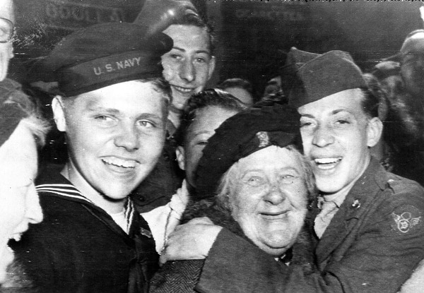 An American soldier, right, hugs an Englishwoman as other U.S. troops celebrate the surrender of Germany, May 7, 1945, in London's Piccadilly Circus. (AP)