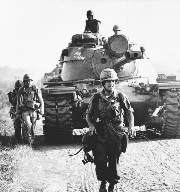 In this 1967 photo, AP correspondent Peter Arnett walks in front of a U.S. tank in Vietnam. (AP Photo)