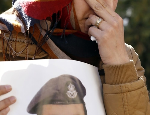 Anwar al-Tarawneh, the wife of Jordanian pilot, Lt. Muath al-Kaseasbeh, who is held by Islamic State group militants, holds a poster of him as she weeps during a protest in Amman, Jordan, Tuesday, Feb. 3, 2015. An online video released Tuesday, Feb. 3, 2015 purportedly shows a Jordanian pilot captured by the Islamic State extremist group being burned to death. The Associated Press was not immediately able to confirm the authenticity of the video, which was released on militant websites and bore the logo of the extremist group's al-Furqan media service. (AP Photo/Raad Adayleh)