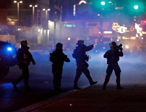 Police walk through tear gas as they try to disperse protesters in Las Vegas, Nev., on May 30, 2020. Three men were accused of planning a terror attack during recent Las Vegas protests. (John Locher/AP)