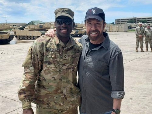 Spc. Freddy Beningo Delacruz Jr., pictured with martial artist and actor Chuck Norris here, was one of three victims found shot dead in an apartment near Fort Hood on March 14, 2020. (Facebook)
