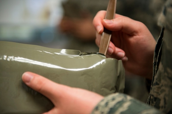Airman McKenzie Daigle, a 23rd Aerospace Medicine Squadron public health technician, gets ready to eat a spoonful of her MRE during an MRE open-package inspection, April 6 at Moody Air Force Base, Ga. Airmen from Public Health examine the MREs for defects and overall quality. (Airman 1st Class Erick Requadt/Air Force)