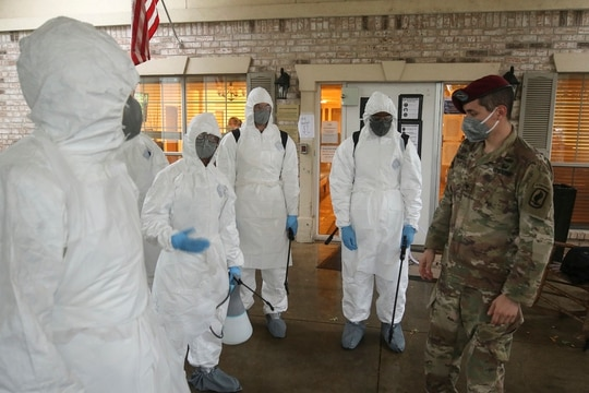 Army National Guard Spc. Joel Mendoza, a chemical, biological, radiological, and nuclear specialist with the 1st Battalion (Airborne) of the 143rd Infantry Regiment, advises members of Joint Task Force 176 on proper wear of personal protective equipment in preparation for disinfecting the West Oaks Nursing and Rehabilitation Center in Austin, Texas, May 12, 2020. (Staff Sgt. Michael Giles/Army National Guard)