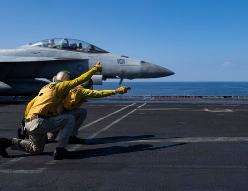 Sailors signal as a F/A-18F Super Hornet launches off the flight deck of the aircraft carrier Nimitz in December 2020. (MC3 Cheyenne Geletka/Navy)