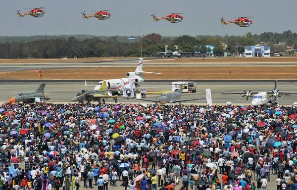 Crowds watch an aerial performance by Sarang (Peacock) ALH helicopters of the Indian Air Force on the penultimate day of the five-day Aero India 2015 air show at Yelahanka Air Force Station in Bangalore on February 21, 2015. AFP PHOTO/Manjunath KIRAN (Photo credit should read MANJUNATH KIRAN/AFP/Getty Images)