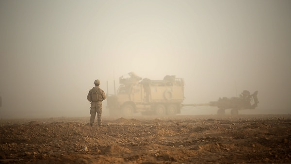 A U.S. Marine waits to guide a troop movement armored vehicle (TMAV) towing an M777-A2 Howitzer to a firing position in Syria, May 14, 2017. (Sgt. Matthew Callahan/Marine Corps)