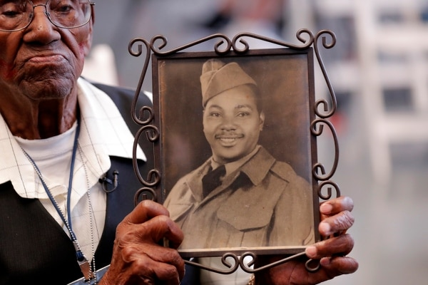 World War II veteran Lawrence Brooks holds a photo of himself taken in 1943 as he celebrated his 110th birthday at the National World War II Museum in New Orleans, Thursday, Sept. 12, 2019. (Gerald Herbert/AP)