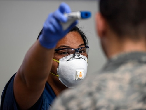 An employee of the 735th Air Mobility Squadron passenger service tests a no-touch thermometer on an airman at the passenger terminal at Joint Base Pearl Harbor-Hickam in Hawaii on March 25, 2020. (Tech. Sgt. Anthony Nelson Jr./Air Force)
