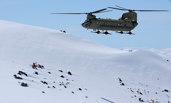 In this photo taken May 15, 2015, a U.S. Army Reserve Boeing CH-47F Chinook helicopter approaches two U.S. Air Force pararescue specialists anchored in the show about 9,000 feet above sea level at Mount Rainier in Washington state during a search and rescue training mission. Army reserve soldiers, and Air Force specialists were training to work along with National Parks Service officials to offer assistance when climbers are lost or injured on the mountain, which is a popular climbing destination. (AP Photo/Ted S. Warren)