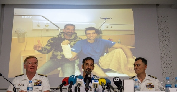 Spanish surgeon Dr. Pedro Cavadas, center, successfully reattached the right hand of a U.S. sailor who suffered a harrowing industrial accident aboard the submarine Georgia off the Spanish coast in March. In the background is a photo of Cavadas and the sailor after the successful surgery. (MC2 Jonathan Nelson/Navy)
