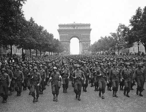In this Aug. 29, 1944 file photo, U.S. soldiers of Pennsylvania's 28th Infantry Division march along the Champs Elysees, with the Arc de Triomphe in the background, four days after the liberation of Paris, France. The fighting for the liberation of Paris took place from Aug. 19 to Aug. 25, 1944. (Peter J. Carroll, AP)