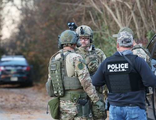 Police, including officials with the U.S. Naval Criminal Investigative Service (NCIS) ,continue with ongoing presence in the community on Nov. 15 while searching for murder suspect Michael Brown. (Heather Rousseau/The Roanoke Times via AP)