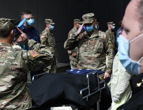 New York Army National Guard Sgt. Maj. Nicholas Pardi, a member of the 104th Military Police Battalion, presents an American flag during a memorial service for a veteran who died of COVID-19 while a patient at the Javits New York Medical Station erected at the Jacob Javits Convention Center in New York City on April 19, 2020. (Maj. Patrick Cordova/Air National Guard)