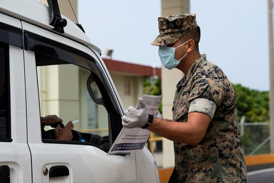 U.S. Marine part of the Security Augmentation Force conduct health and wellness checks of pool individuals entering Camp Foster in an effort to combat the spread of COVID-19, on Camp Foster, Okinawa, April 3. (Cpl. Kameron Herndon/Marine Corps)