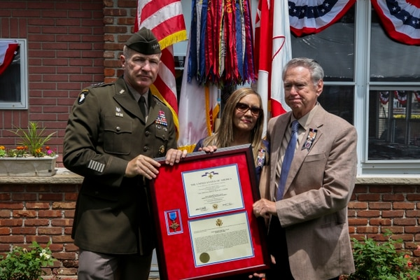 Robert Ollis, the father of Staff Sgt. Michael Ollis, and Kimberly Loschiavo, the soldier's sister, receive the Distinguished Service Cross from Army Vice Chief of Staff Gen. James McConville on June 8. (Sgt. Jerod Hathaway/Army)