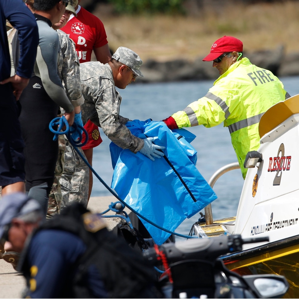 Water safety officials hand over possible debris from an Army UH-60 Black Hawk helicopter crash to military personnel stationed at a command center in a harbor on Aug. 16, 2017, in Haleiwa, Hawaii. (Marco Garcia/AP)